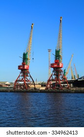 KALININGRAD, RUSSIA - JUNE 4, 2015: Two portal Ganz cranes in the Kaliningrad sea trade port in the summer evening