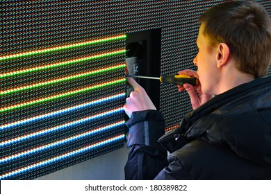 KALININGRAD, RUSSIA - MARCH 7, 2014: Electrician repair the damaged item in large advertising LED screen on the street