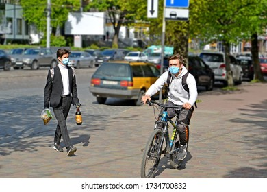 KALININGRAD, RUSSIA - MAY 15, 2020: Cyclist and pedestrian wearing protective masks on the city street. Coronavirus epidemic COVID-19 in Russia
