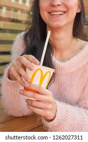 KALININGRAD, RUSSIA - OCTOBER 13, 2018: young woman with paper cup of Coca-Cola at McDonald's restaurant.
