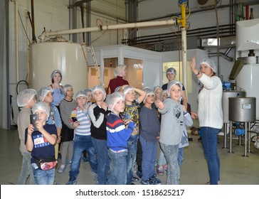 KALININGRAD, RUSSIA - SEPTEMBER 27, 2019: A tour guide shows children equipment in a manufacturing shop. Children s tour to the chocolate factory BELGOSTAR