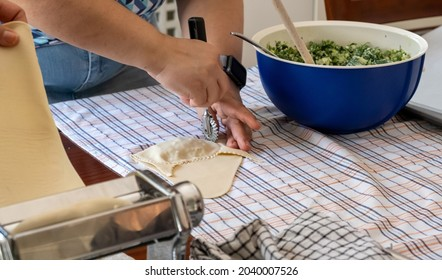 Kalitsounia preparation concept. Dough sheeter machine bowl with filling ingredients table kitchen towel for preparing of uncooked pies Cretan housewives is the secret receipt for delicious kaltsounia