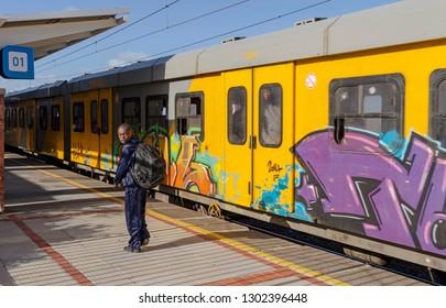 Kalk Bay, Cape Town, South Africa. Circa 2017. A young schoolboy leaving a yellow metro passenger train at Kalk Bay station
