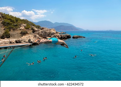 KALKAN, TURKEY - JULY, 08, 2016: Young man is jumping into the sea from the yacht, Antalya