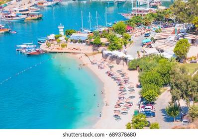 KALKAN, TURKEY - JULY 29, 2017: Holidaymakers sunbathing at Kalkan beach,