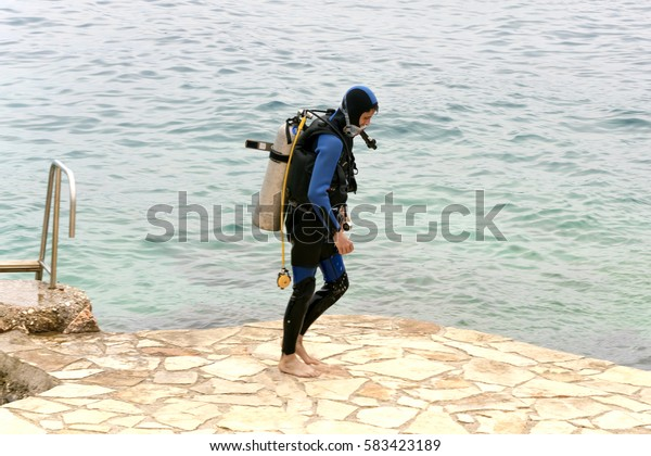 Kalkan, Turkey, May 5, 2016: Diver walking on the sidewalk near the sea