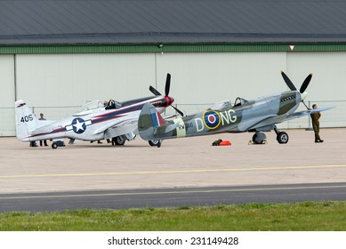 KALLINGE, SWEDEN - JUNE 01, 2014: Swedish Air Force air show 2014 at F 17 Wing. North American P-51 Mustang and Supermarine Spitfire airborne near the hangar.