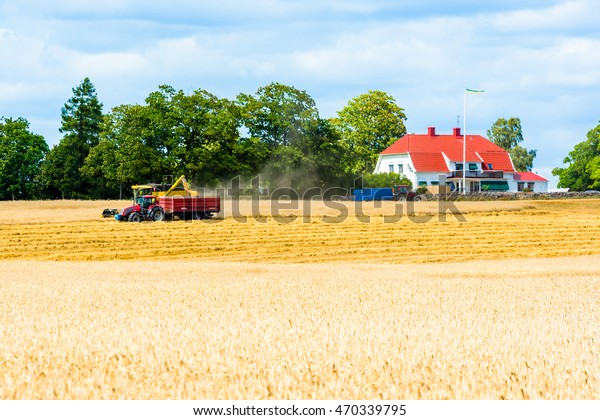 Kalmar, Sweden - August 10, 2016: Harvester emptying crop into tractor trailer. Farmhouse and other tractor in background.