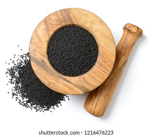 kalonji seeds in the wooden mortar, isolated on the white background, top view
