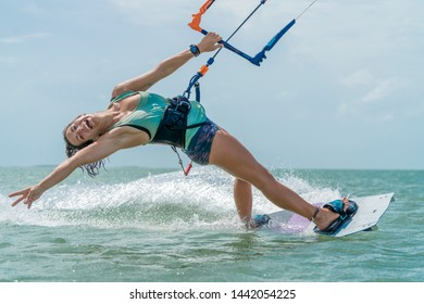 Kalpitiya Sri Lanka - 10.06.2019: Young beautiful girl posing during her kitesurfing session in Sri Lanka while splashing the water in the background