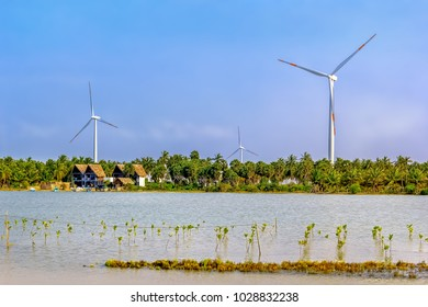 Kalpitiya, Sri Lanka - January 2, 2018. Wind turbines stand in the jungle on the shore of the lake on a sunny day