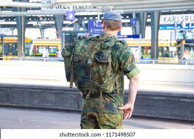 Kalsruhe/Germany -July 27 2018: Young soldier wearing military camouflage clothes  and working in the German army is taking the train home for his weekend off to visit his family and friends back home