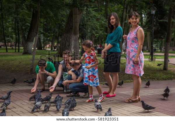 KALUGA, RUSSIA - 14 JULY 2013 - An unidentified group of people, probably family are feeding pigeons at a park of Tver city