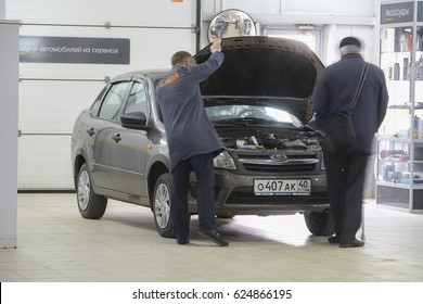 Kaluga, Russia - April, 20, 2017: The elderly owner of the car and the master-receiver inspect the car before repair in the dealer center in Kaluga, Russia