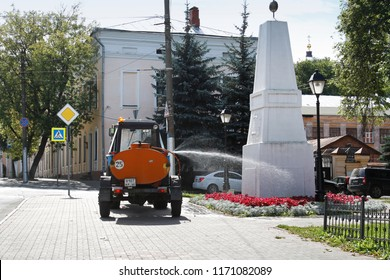 Kaluga, Russia - August 13, 2018: Worker on a tractor with a tank watering a flower bed on the street in Kaluga