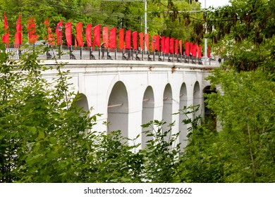 Kaluga, Russia - May 11, 2019: View of Stone arch bridge across the Berezuysky ravine with red flags