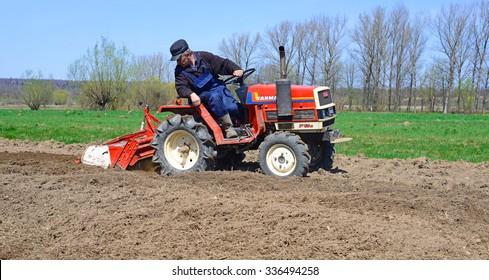 Kalush, Ukraine April 23: Farmer on tractor handles field near the town Kalush, Western Ukraine April 23, 2015