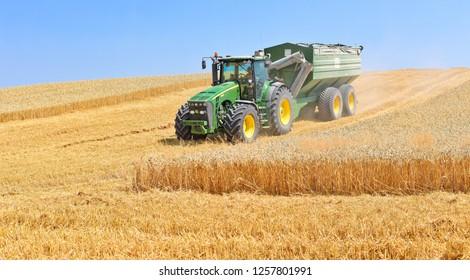 Kalush, Ukraine August 2, 2017: Modern tractor with a trailer for harvesting grain near the town Kalush, Western Ukraine.