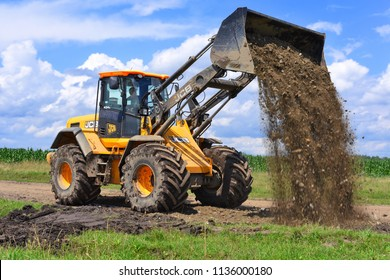 Kalush, Ukraine  July 12, 2017: The JCB bucket loader is repairing a section of a dirt road near the town of Kalush, Western Ukraine.
