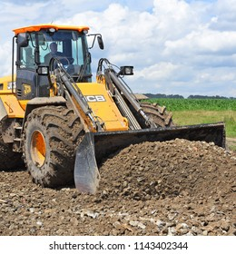 Kalush, Ukraine  July 12, 2018: The JCB bucket loader is repairing a section of a dirt road near the town of Kalush, Western Ukraine.