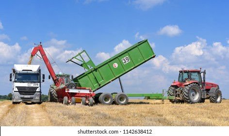 Kalush, Ukraine  July 20, 2018: Loading grain from grain trailer into the body of a large-capacity truck with a screw-type loader near the town Kalush, Western Ukraine.