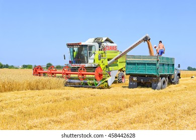 Kalush, Ukraine - July 23: Overloading the grain from the combine into a car in the field near the town Kalush, Western Ukraine July 23, 2015