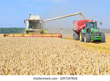 Kalush, Ukraine - July 28, 2016: Overloading grain harvester in tractor trailer tank in the field near the town Kalush, Western Ukraine