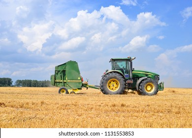 Kalush, Ukraine - July 28, 2016: Universal tractor harvesting straw in the field near the town Kalush, Western Ukraine