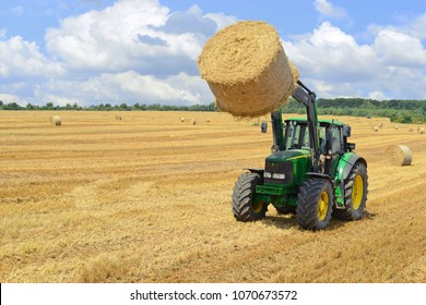 Kalush, Ukraine - July 30, 2016: Moving bales of straw tractor with machining attachments in the field near the town Kalush, Western .