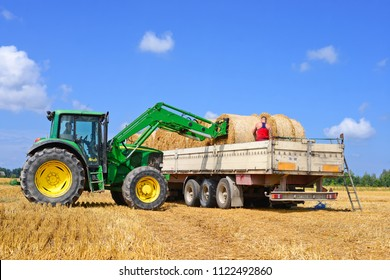 Kalush, Ukraine - July 30, 2016: Loading bales of straw in the car tractor with attachments in the field near the town Kalush, Western Ukraine
