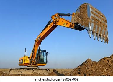 Kalush, Ukraine â?? October 14: Modern JCB excavator on the highway pipeline performs excavation work in the field near the town Kalush, Western Ukraine October 14, 2014