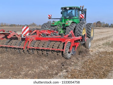 Kalush, Ukraine - October 16, 2019: Kalush, Ukraine - October 1, 2019: A modern John Deere tractor with trailed equipment processes the soil before sowing grain in a field near the city of Kalush.