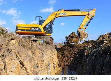 Kalush, Ukraine October 7: Modern JCB excavator on the highway pipeline performs excavation work in the field near the town Kalush, Western Ukraine October 7, 2014