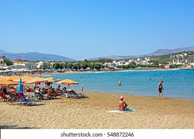 KALYVES, CRETE - SEPTEMBER 16, 2016 - Tourists relaxing on the beach with views towards the mountains, Kalyves, Crete, Greece, Europe, September 16, 2016.
