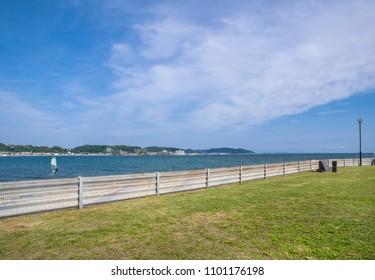 "KAMAKURA CITY, KANAGAWA / JAPAN - MAY 11 2018 : Scenery of ""Kamakura Kaihin Park"". It is called Sakanoshita district. It faces the ocean, overlooking the ""Yuigahigahama"" beach and surfers."