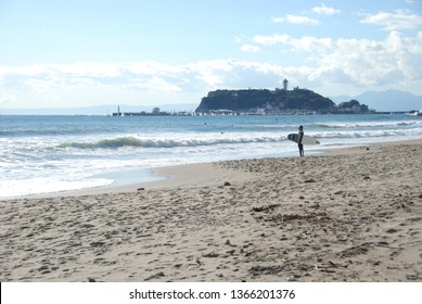 Kamakura, Japan - 11/19/2017: A surfer waiting for a wave on sandy Koshigoe Beach with Enoshima island and Sea Candle tower in the background