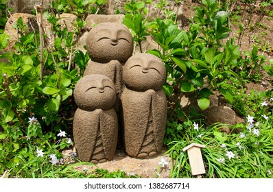 KAMAKURA, JAPAN - APRIL 05, 2019: Stone statue of three smiling Jizo (Nagomi Jizo), Hasedera temple, Kamakura, Japan