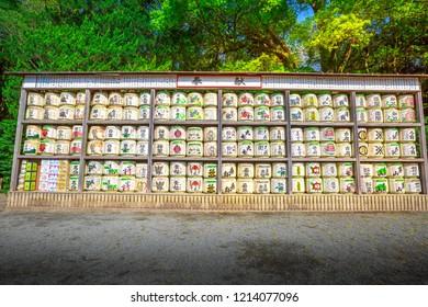 Kamakura, Japan - April 23, 2017: a lot of Japanese sake rice wine barrels with decorative writing in Tsurugaoka Hachiman Shinto shrine in Kamakura. Sake is an alcoholic beverage of Japanese.