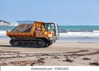 KAMAKURA, JAPAN - CIRCA APR, 2013: Crawler transporter full of sand drives on sandy beach on coast of Pacific ocean. Municipal beach improvement works. Side view