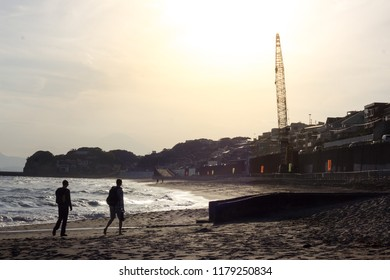 Kamakura, Kanagawa / Japan - July 8th 2015: Two Tourists Walking On Kamakura Beach At Sunset