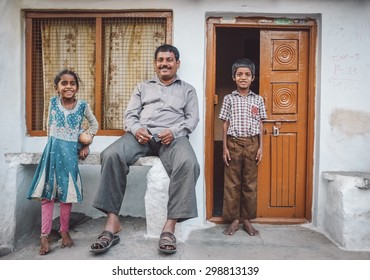 KAMALAPURAM, INDIA - 02 FABRUARY 2015: Father and his two children in front of their home in a town close to Hampi. Post-processed with grain, texture and colour effect.