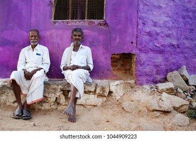KAMALAPURAM, INDIA - 02 FEBRUARY 2015: Local Indian men resting and socialising on the street in front of a purple coloured home.