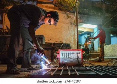KAMALAPURAM, INDIA - 02 FEBRUARY 2015: Indian worker welding heavy metal parts on street in dusk