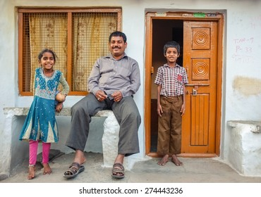 KAMALAPURAM, INDIA - 02 FEBRUARY 2015: Father and his two children infront of their home in a town close to Hampi