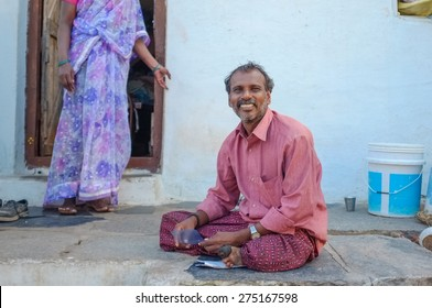 KAMALAPURAM, INDIA - 02 FEBRUARY 2015: Indian man sitting infront of house in a town close to Hampi