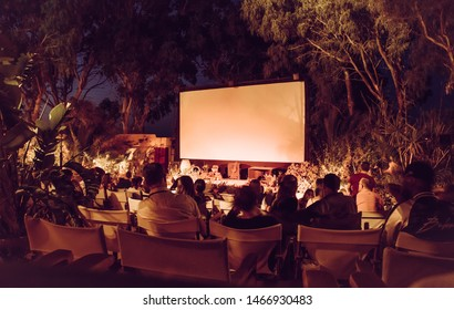Kamari, Santorini / Greece: 18JUL2019:Santorini, Kamari town open air cinema. People waiting movie to begin in no roof and open air movie theater. Vintage Instagram style picture.