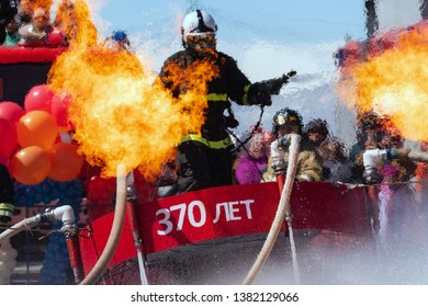 KAMCHATKA PENINSULA, RUSSIA - APR 27, 2019: Rescue firefighter Emercom of Russia flying with flamethrowers, spewing flames. Celebration of Day of Fire Protection of Russia (soft focus, blur from fire)