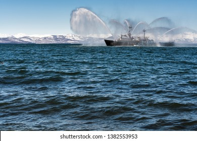 KAMCHATKA PENINSULA, RUSSIA - APR 27, 2019: Rescue and salvage ship of Pacific Fleet of Russia spraying water on sea for supporting emergency case of fire of warships, cargo and passengers ships