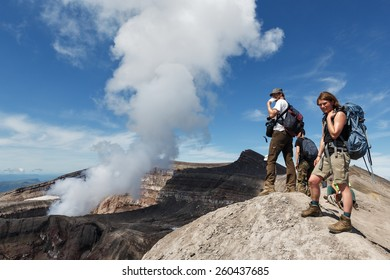 KAMCHATKA PENINSULA, RUSSIA - JULY 21, 2013: Group of tourists and travelers stand on top of active Gorely Volcano watching at work of volcano fumaroles, erupting cloud of steam and gas from crater.