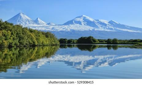 Kamchatka Peninsula. Russia.  Kluchevskaya group of volcanoes with reflection in the river Elovca.The volcano of Klyuchevskaya sopka. (4800 m) is the highest active volcano of Eurasia.